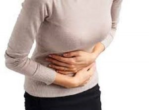 Person holding stomach with cramps.